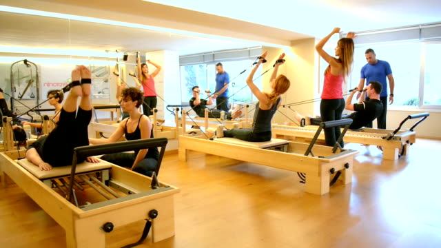 dolly: group of people exercising with pilates machines - pilates stock videos and b-roll footage