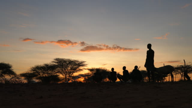 group of people gathering and sitting on the ground at sunset / ethiopia, africa - indigenous culture stock videos & royalty-free footage