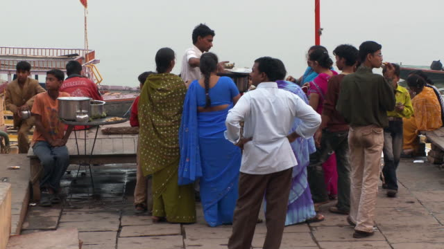 Group of people getting food to eat at the wharf in an Indian town.