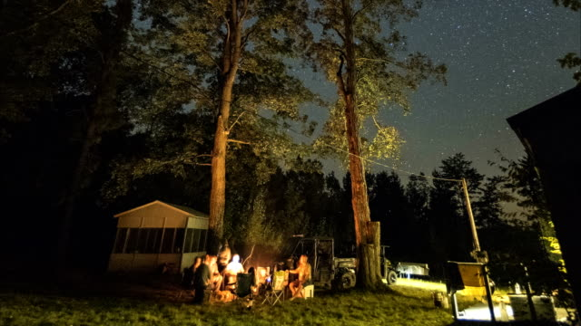 group of people hanging out around a campfire on a beautiful summer night - summer camp stock videos & royalty-free footage
