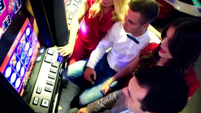 vidéos et rushes de groupe de personnes s'amuser au casino. - machine à sous