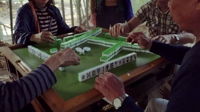 group of people in a park sitting around table playing mahjong, sham shui po district, kowloon, hong kong - tischflächen aufnahme stock-videos und b-roll-filmmaterial