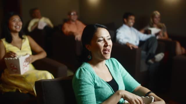 ms group of people in movie theater watching comedy and eating popcorn / bellevue, washington, usa - biosalong bildbanksvideor och videomaterial från bakom kulisserna