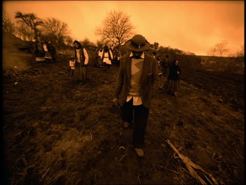 sepia group of people in native dress walking toward camera in muddy field / sibiu, transylvania - transylvania stock videos & royalty-free footage