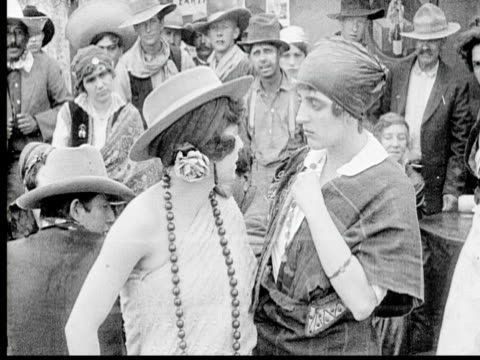 vidéos et rushes de b/w 1920 ms group of people in saloon, showgirl throwing beer at woman - agression