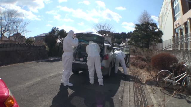 group of people in the mandatory exclusion zone put on protective garments before entering deserted buildings after fukushima daiichi nuclear plant... - abandoned stock videos & royalty-free footage