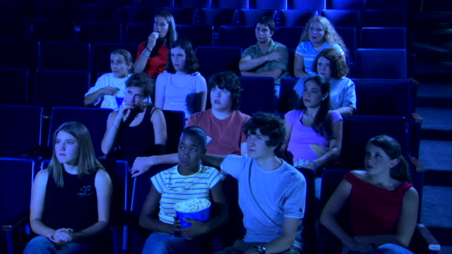 a group of people lean toward the movie screen and jump as they watch a scary movie in a theater. - biosalong bildbanksvideor och videomaterial från bakom kulisserna