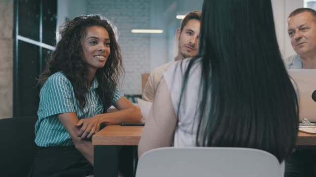 vídeos y material grabado en eventos de stock de grupo de personas que escuchan su charla de compañero de trabajo durante una reunión de negocios - mesa negociadora