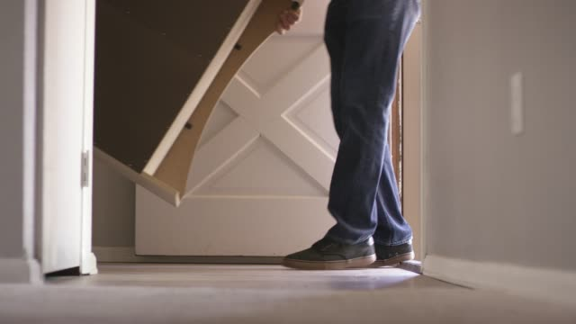 a group of people move furniture out a front door - sollevare video stock e b–roll