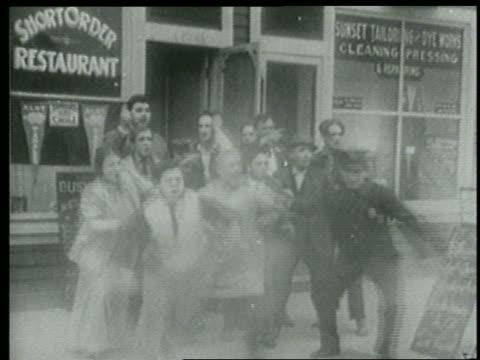 b/w 1915 group of people on sidewalk, including keystone kops, rushing toward something offscreen - 1915年点の映像素材/bロール