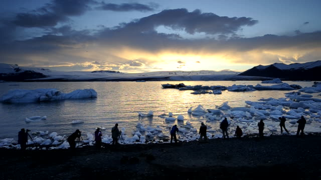 group of people on the banks of the jokulsarlon lagoon at sunset. iceland. - jokulsarlon stock-videos und b-roll-filmmaterial