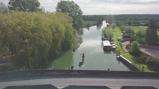 group of people paddling kayaks and passing under the stone bridge in river thames with green nature scenery in abingdon town near oxford city, uk. - aerial drone shot - barge stock videos & royalty-free footage
