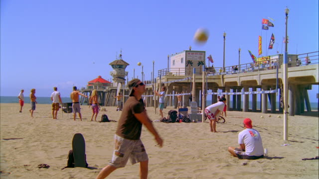 ws zi zo group of people playing beach volleyball, pier in background / huntington beach, california, usa - huntington beach california stock videos and b-roll footage