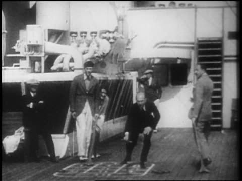 vídeos y material grabado en eventos de stock de b/w 1928 group of people playing shuffleboard on deck of ocean liner / newsreel - 1928