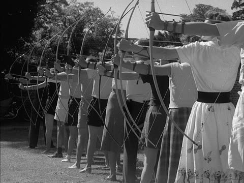 A group of people practice archery in a garden 1953