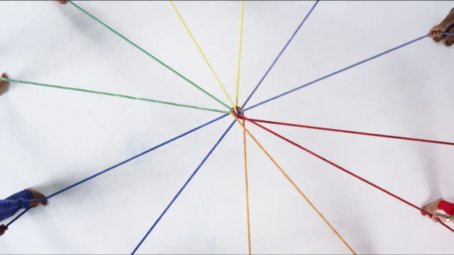 Group of People Pull on Ropes of Various Colors in Opposite Directions