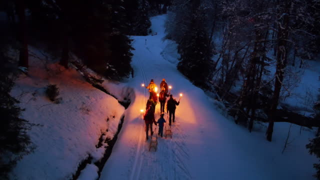 group of people pulling toboggan sleds up snowy road at night with lanterns - lantern stock videos & royalty-free footage