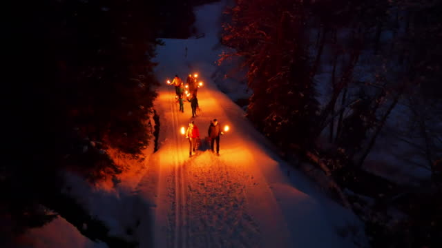 Group of people pulling toboggan sleds up snowy road at night with lanterns