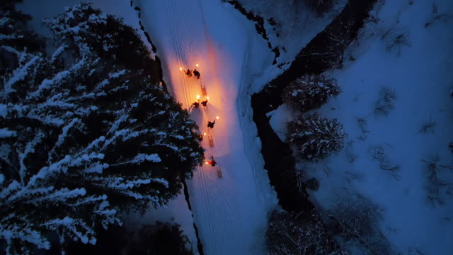 group of people pulling toboggan sleds up snowy road at night with lanterns - lanterna attrezzatura per illuminazione video stock e b–roll