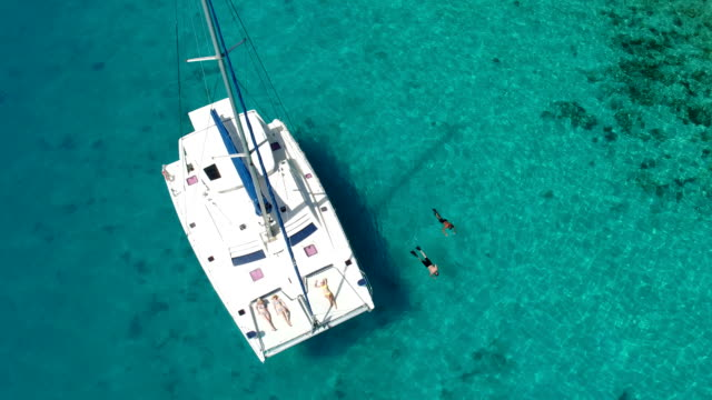 group of people relaxing and snorkeling from luxury catamaran