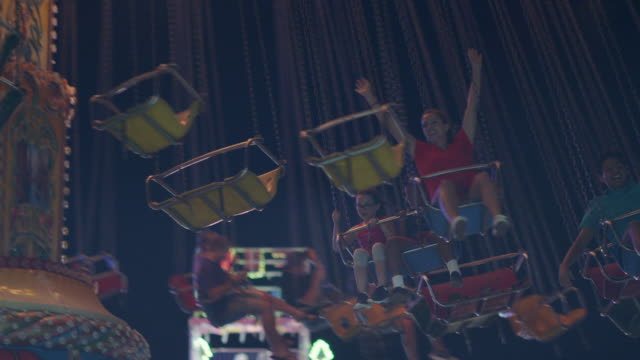 slow mo. a group of people ride swings at a summer carnival - amusement park stock videos & royalty-free footage