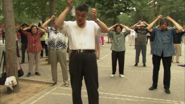 vídeos de stock, filmes e b-roll de ws pan group of people rubbing faces during morning ritual in yuyuantan park, beijing, beijing, china - com as mãos na cabeça