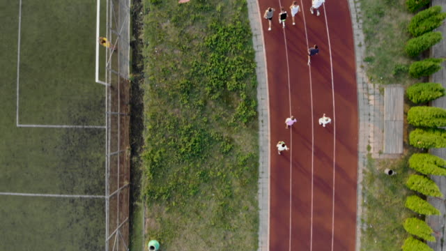 group of people running on a running track - pista di atletica leggera video stock e b–roll