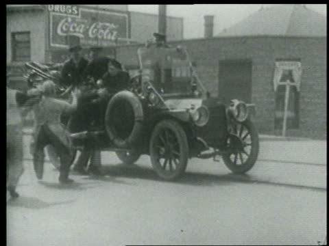 stockvideo's en b-roll-footage met b/w 1915 group of people rushing to keystone kops in car + pointing on city street / short - 1915