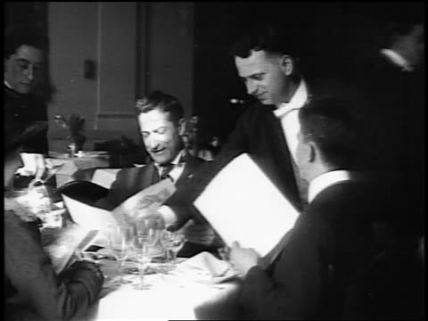 b/w 1916 group of people seated at table in restaurant looking at menus as waiters pour them water - 1916 stock videos & royalty-free footage