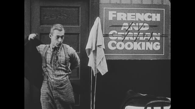 "1918 a group of people sit down at a restaurant table, and a man puts on an apron next to a sign that reads ""french and german cooking"" with ""and german"" crossed out - french food stock videos and b-roll footage"