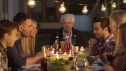 Group of People Sitting Around a Table, Eating, Communicating and Having Fun during Family Dinner.