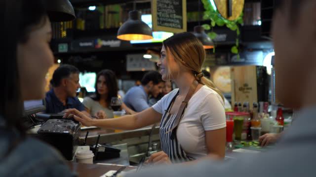 vídeos de stock e filmes b-roll de group of people sitting around the bar counter enjoying drinks and food talking and smiling - empregada de mesa