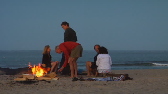 MS, Group of people sitting at bonfire on beach, North Truro, Massachusetts, USA