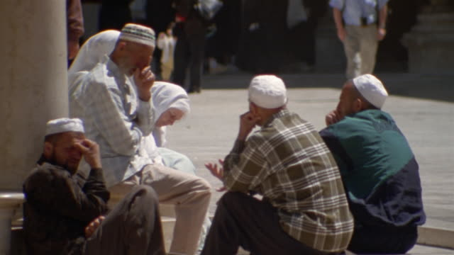 MS, group of people sitting by column on street, pedestrians walking in background, Damascus, Syria