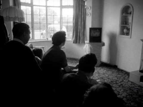 A group of people sitting in a lounge watch the Coronation proceedings on a television