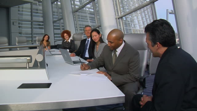 ms group of people sitting in modern office conference room as man signs contract/ two managers standing and shaking hands/ virginia beach, virginia - contract stock videos & royalty-free footage