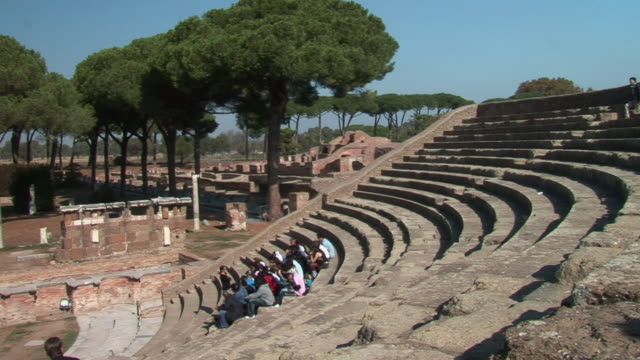 stockvideo's en b-roll-footage met ws group of people sitting on steps in the ruins of an ancient amphitheater / ostia, lazio, italy - amfitheater
