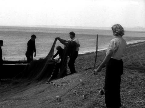 group of people sort out fishing nets on chesil beach in preparation for fishing for mackerel. 1956. - 1956 stock-videos und b-roll-filmmaterial