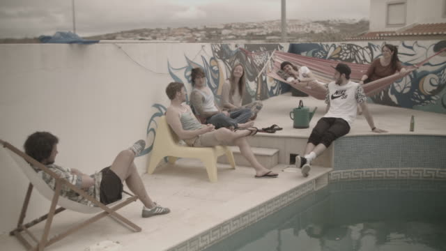 group of people spending time together by the swimming pool at a surf camp - bande stock-videos und b-roll-filmmaterial