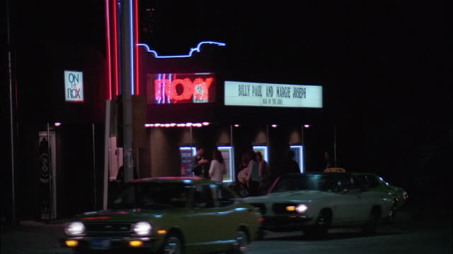 group of people standing at roxy club, cars riding on street, night, los angeles - sunset boulevard stock-videos und b-roll-filmmaterial
