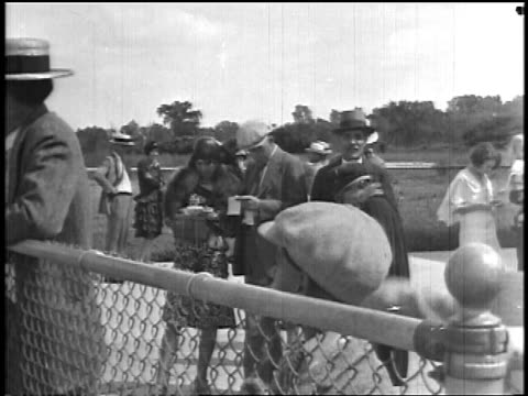 stockvideo's en b-roll-footage met b/w 1927 group of people standing by chain link fence outdoors looking at airline tickets / newsreel - 1927