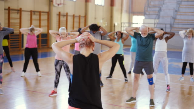 vídeos de stock, filmes e b-roll de grupo de pessoas que esticam após a classe da dança - aula de exercícios