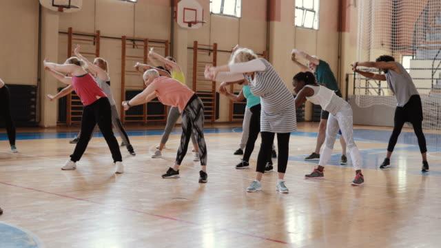 vídeos de stock, filmes e b-roll de grupo de pessoas que esticam antes da classe da dança - aula de exercícios