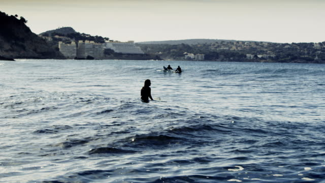 group of people surfing in the sea. sun reflecting in waves - bay of water stock videos & royalty-free footage