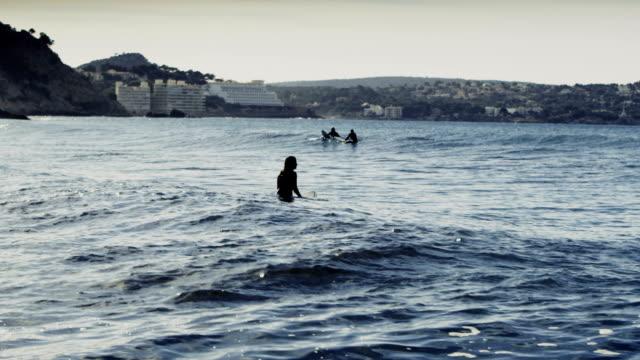Groep mensen surfen in de zee. Zon weerspiegelt in golven