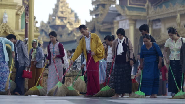 Group of people sweep temple square in Myanmar