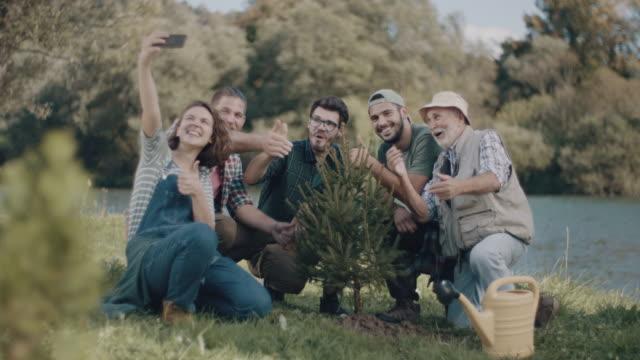 vídeos de stock e filmes b-roll de group of people taking selfie by new tree - plantar