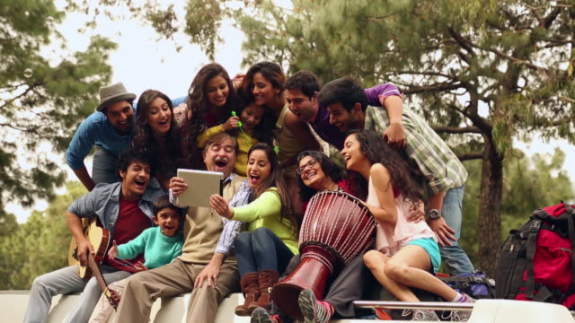 Group of people taking selfie picture with a digital tablet  on the roof of the bus, Shimla, Himachal Pradesh