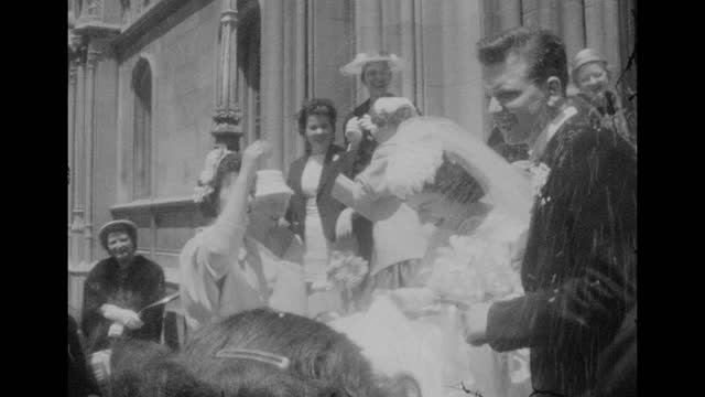 a group of people throw rice at two newlyweds after they get married in a church. - black and white stock videos & royalty-free footage
