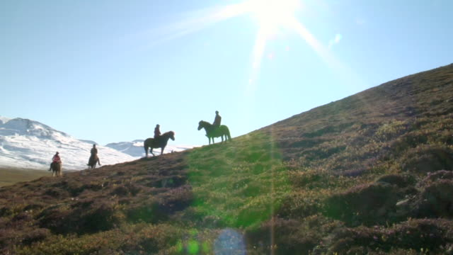MS Group of people trot on horseback on mountain side with sun / Skagafjorour, Nordhurland Vestra, Iceland